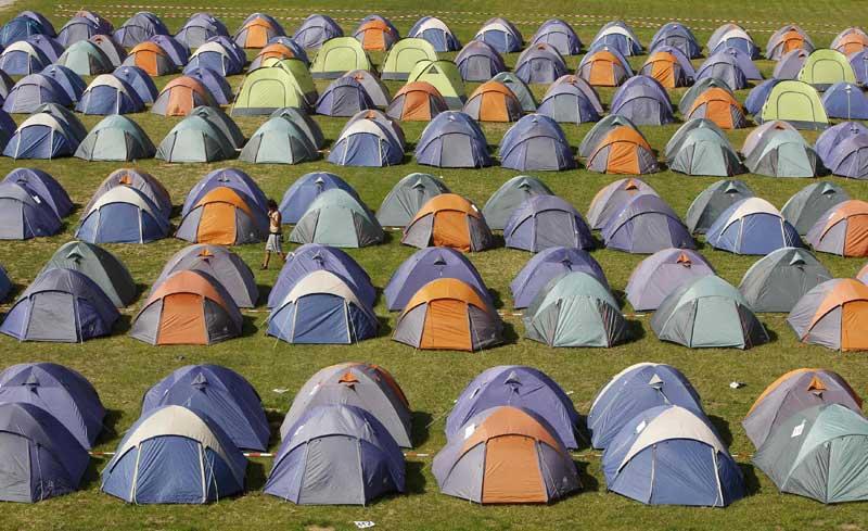 Alemanha, Munique, 13.09.2011 | Um homem caminha por um campo com três centenas de tendas, no Wies'n Camp, a 10 minutos do local onde se vai realizar mais uma edição da megafesta da cerveja Oktoberfest. No Wies'n, pode alugar-se uma tenda para quatro por 58 a 68 euros. A Oktoberfest decorre de 17 de Setembro a 3 de Outubro.