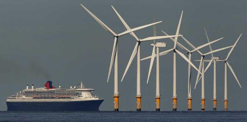 Reino Unido, 15.09.2011 | O navio de cruzeiros Queen Mary 2 (Royal Caribbean) passa pelas eólicas marinhas colocadas em Burbo Bank.