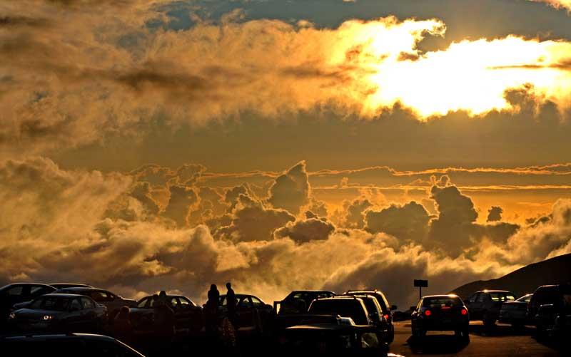 EUA, Havai, 11.09.2011 | Pôr-do-sol sobre o parking: os visitantes admiram o sol a descer sobre o Haleakala, um grande vulcão do Parque Nacional Haleakala no Maui, Havai.