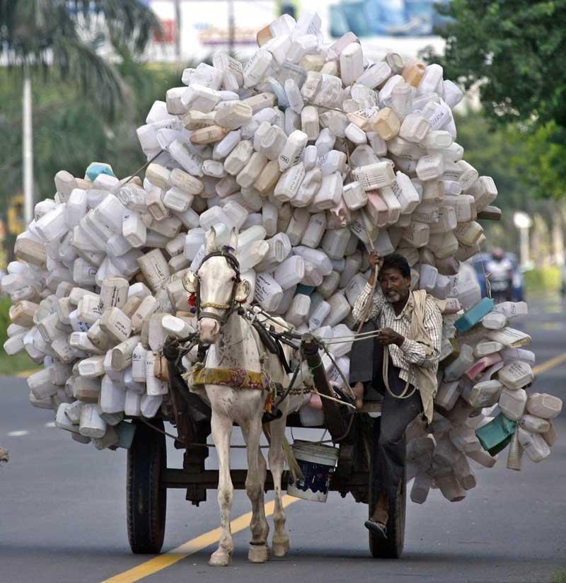 Índia, Haryana, 21.09.2011 | Cabe sempre mais uma na carroça deste trabalhador indiano: transporta centenas de embalagens para a sucata em Panchkula.
