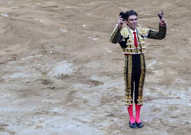 O toureiro Jose Tomas, aplaudido pelos espectadores (nas suas mãos estão duas orelhas cortadas ao touro).