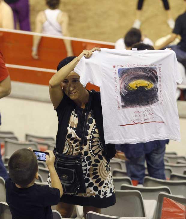 O filho fotografa a mãe, uma aficionada que conseguiu uma das t-shirts com o último cartaz. Cartazes, t-shirts e outros