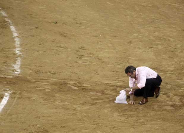 Um aficionado aproveita para recolher areia da arena como recordação.