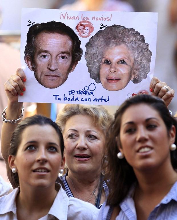 Uma mulher levanta um cartaz de apoio aos noivos por entre a multidão que esperava fora do palácio de Las Dueñas, onde se realizou o casamento entre a Duquesa de Alba, Cayetana Fitz-James Stuart y Silva, e Alfonso Díez