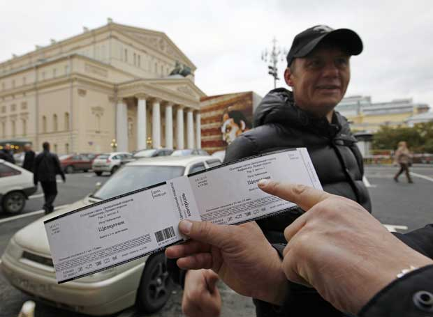 O privilégio da entrada: um futuro espectador mostra o seu bilhete para uma sessão do