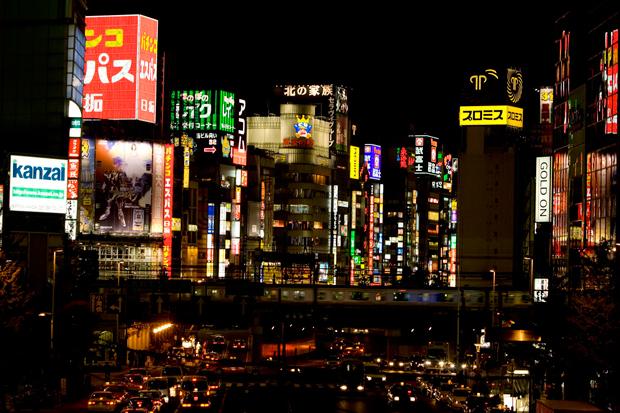 """O bairro de Shinjuku à noite na zona de Kabukicho. O frenesim de néons atinge o seu esplendor. Uma zona de passagem intensa de pessoas e tráfego, um cenário nocturno digno do filme """"Blade Runner""""."""