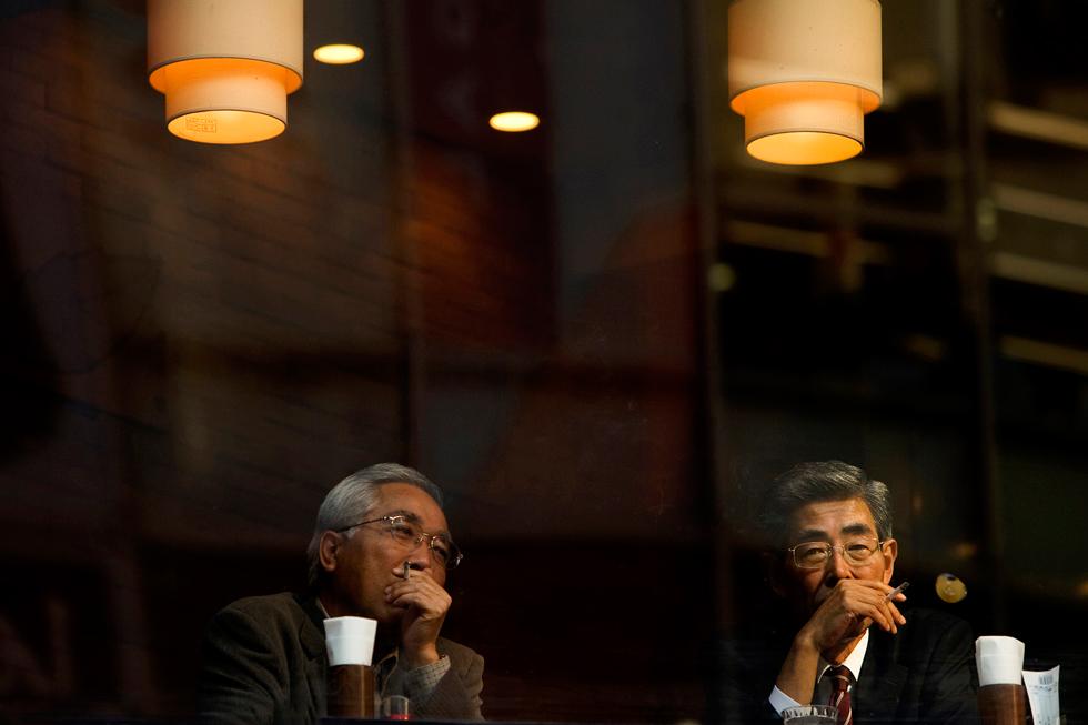 Dois executivos na zona de Roppongi, um dos bairros mais exclusivos da cidade, numa pausa para um cigarro. É proibido fumar nas ruas em Tóquio, no exterior apenas em zonas devidamente sinalizadas e com cinzeiros. E de preferência com um ecrã gigante em frente a passar publicidade.
