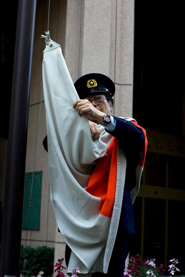 Um polícia hasteia a bandeira num edifício governamental.
