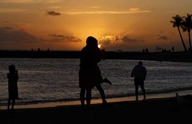 Havai, 9.11.2011 | Um clássico momento romântico: um casal abraça-se ao pôr-do-sol na praia de  Waikiki em Honolulu.