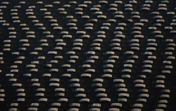 Tailândia, 14.09.2011 | A Tailândia aposta na rapidez da limpeza após as cheias, por todas as razões e para evitar um maior rombo na indústria turística. E noutras: a geometria que se vê na foto resulta de um bloco de automóveis submersos pelas águas numa fábrica da Honda.