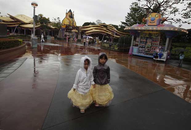 China, Hong Kong, 17.11.2011 | A chuva incomoda mas nao impede esta duas meninas de passearem pela Disneyland de Hong Kong, numa altura em que o parque se expande e estreia uma área Toy Story.