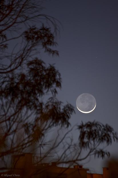 """Lua em fase Crescente, com apenas 3% do disco iluminado e onde é visível um forte """"Earthshine"""" lunar, tornando visível a parte da Lua que nesta fase não se encontra directamente exposta aos raios solares, mas que se torna visível devido à luz reflectida na sua superfície, pelo próprio planeta Terra, que ilumina assim a parte escura da Lua, claramente visível. No Feijó, Almada, em 04/02/2011 às 18h50."""