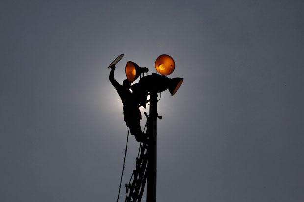 Paquistão, 21.11.2011 | Um trabalhador repara sinais de trânsito num parque em Lahore.