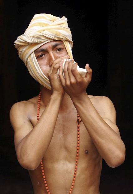 Um homem representando o deus Madhavnarayan sopra uma concha em Thecho, perto de Katmandu, durante o Madhav Narayan Mela, festival dedicado a Madhavnarayan e à deusa Swasthani. Inclui récitas de lendas populares e milagres.