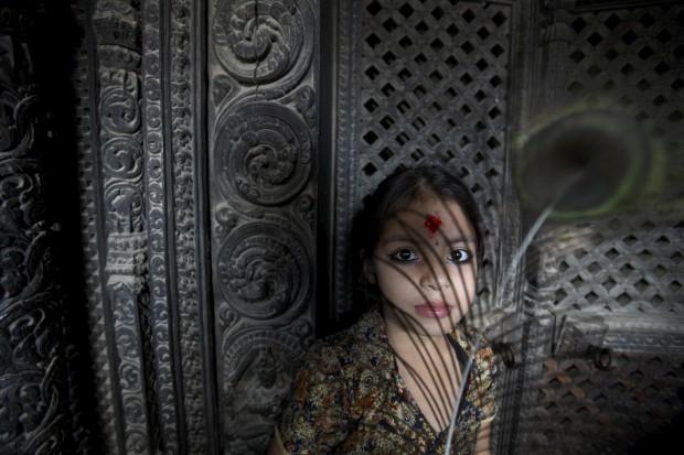 Uma rapariga segura uma pena de pavão durante o festival Krishna Janmashtami, que marca o nascimento do deus. Agosto/2011. Em Lalitpur, perto de Katmandu.