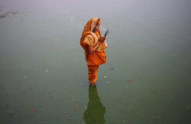Uma devota aguarda pelo nascer do sol para as suas preces no último dia do festival Chhat, em Katmandu, em honra do deus sol.