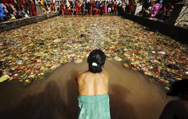 Uma devota prepara-se para o mergulho sagrado no Matathirtha no Dia das Mães em Katmandu. Maio, 2011