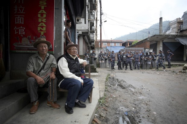 Dois exilados tibetanos, à porta de uma escola tibetana em Katmandu, com agentes da polícia ao fundo. Objectivo: impedir a celebração do aniversário do líder espiritual do Tibete, o Dalai Lama (a 6 de Julho), receando protestos anti-China.