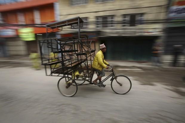 Um homem transporta mercadorias em Katmandu.