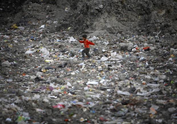 Uma criança brinca numa lixeira, na margem do rio Bagmati, em Katmandu. Novembro, 2011.