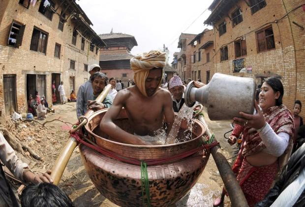 Uma crente oferece água a um homem que representa o deus Madhavnarayan, em Thecho, perto de Katmandu, durante o Madhav Narayan Mela. Fevereiro, 2011.