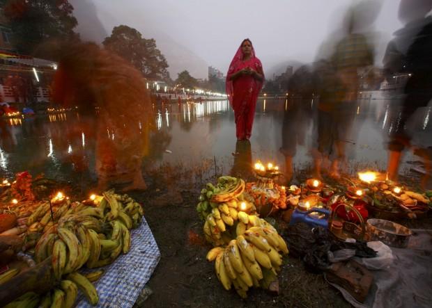 Uma devota aguarda pelo nascer do sol para as suas preces no último dia do festival Chhat, em Katmandu, em honra do deus sol. Novembro, 2011