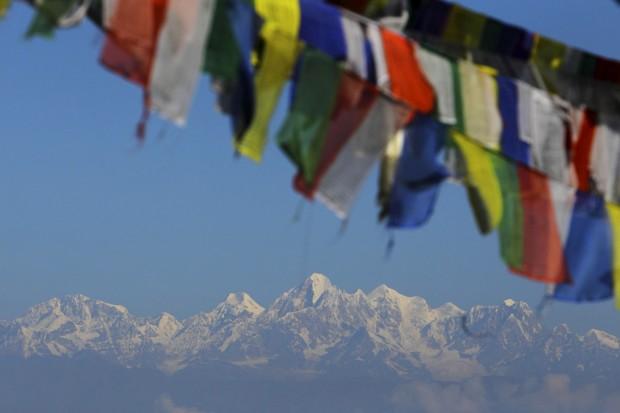 Evereste ao fundo com bandeiras religiosas a ondular ao vento. Vista a partir do mosteiro Thrangu Tashi Yangtse, Kavre, perto de Katmandu.
