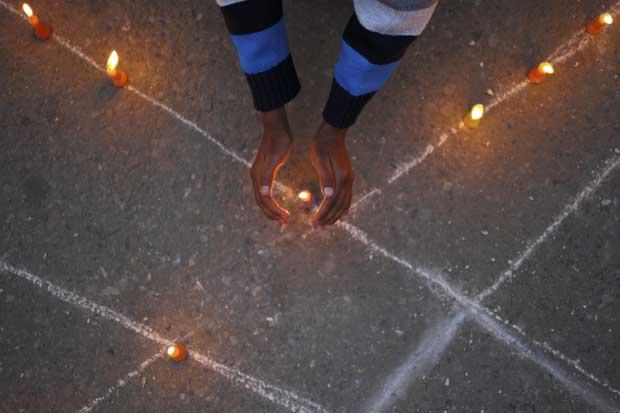 Um jovem tenta proteger a chama de uma vela durante uma cerimónia que marca o dia mundial da luta contra a sida. Novembro, 2011.