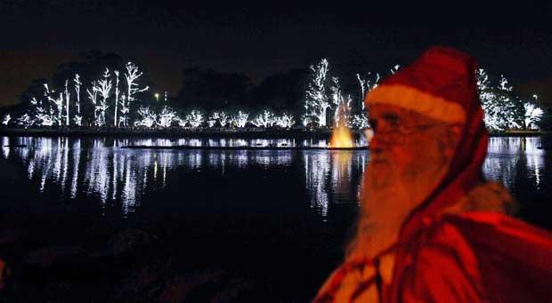 Brasil, 11.12.2011 | Pai Natal, em frente a árvores decoradas com luzes natalícias, no Parque Ibirapuera de São Paulo.
