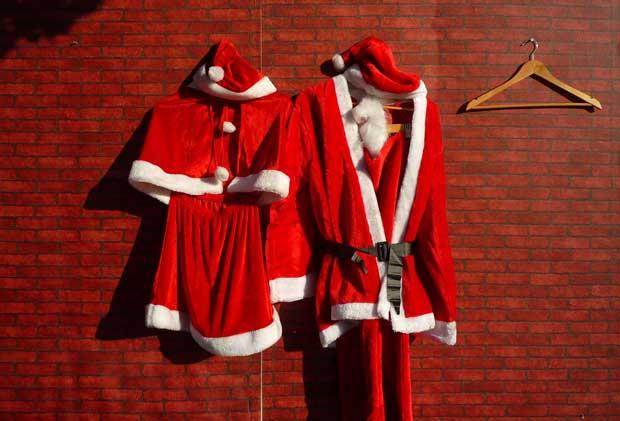 China, 11.12.2011 | Os fatos de mãe e pai Natal aguardam o seu momento num mercado de Pequim.
