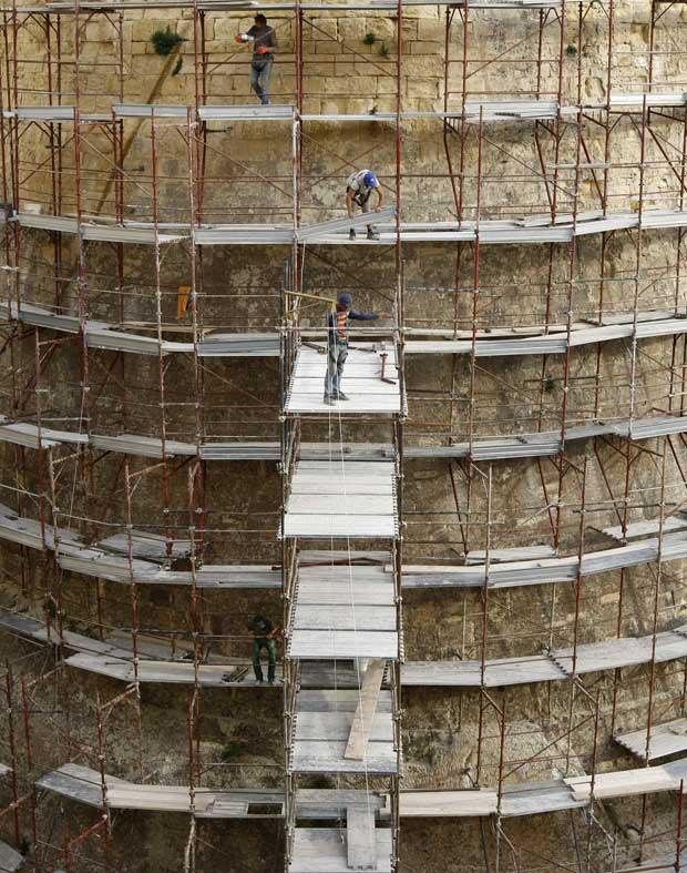 Malta, 10.12.2011 | Trabalhadores num dos andaimes colocados nos baluartes em redor da cidade de Valeta: há trabalhos de restauro dos célebres baluartes ao longo de 6km de fortificações.