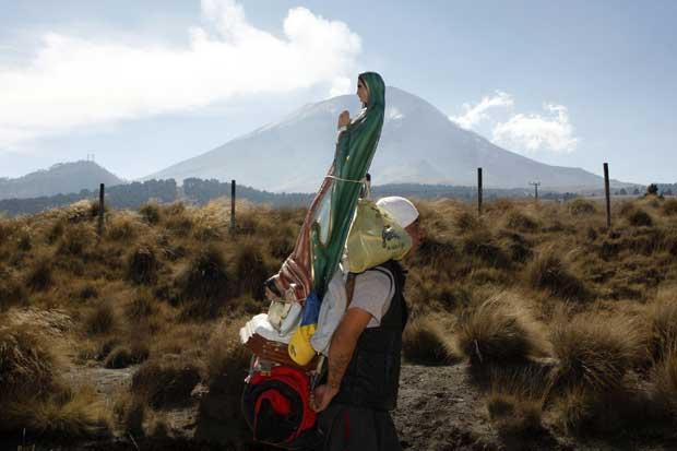 México, 9.12.2011 | A estátua da Virgem da Guadalupe às costas de um peregrino. Milhoes de mexicanos viajam para a Cidade do México para celebrar o dia da Virgem de Guadalupe a 12 de Dezembro.