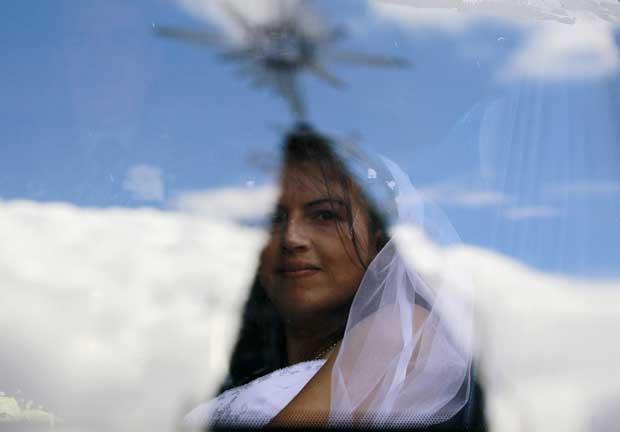 Colômbia, 9.12.2011 | Uma recém-casada observa através da janela de um autocarro (onde se vê o reflexo da Catedral de Bogotá). Foi uma das noivas da cerimónia de casamentos em massa de polícias colombianos: 96 agentes casaram neste dia numa tradição que se repete todos os anos.