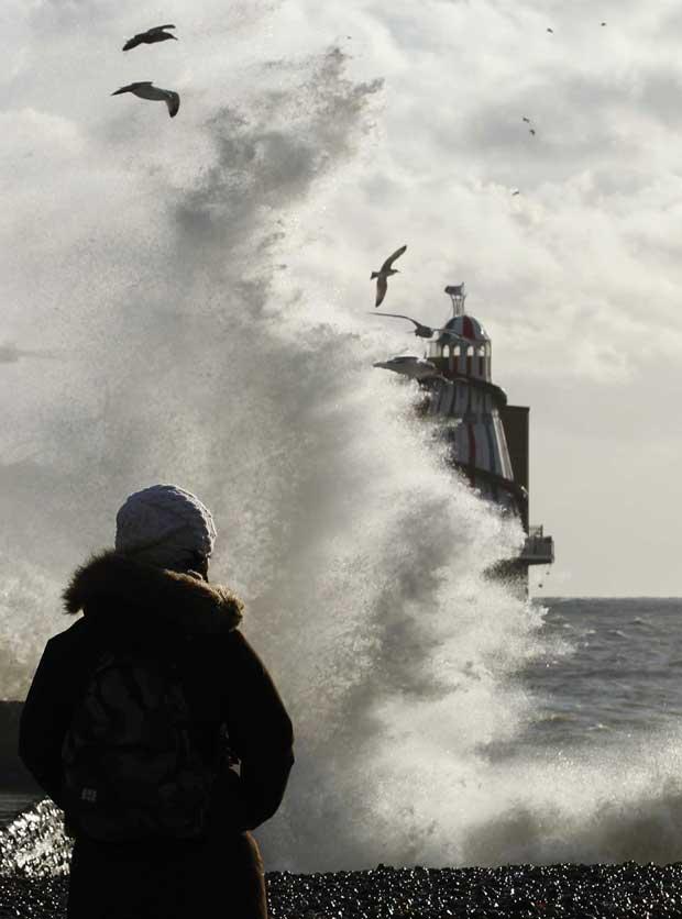 Reino Unido, 15.12.2011 | Uma mulher observa uma onda gigante em Brighton.
