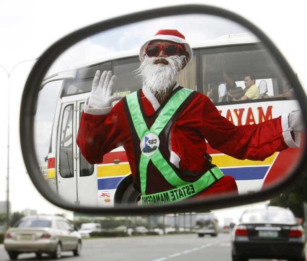 Filipinas, 14.12.2011 | O controlador de tráfego Ramiro Hinojas, em Pasay, decidiu vestir-se de Pai Natal. Aqui, é visto reflectido no espelho lateral de um veículo.