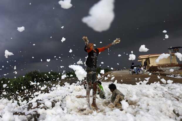 Indonésia, 14.12.2011 | As aparências enganam: as crianças brincam, em Jacarta, com a espuma de um rio poluído.