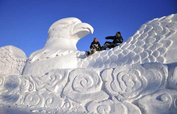 China, 18.12.2011 | Crianças brincam numa águia feita de neve durante o Festival de Esculturas de Neve em Hulun Buir.