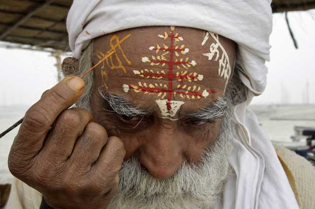 "Índia, 19.12.2011 | Um hindu escreve ""Feliz Natal"" em hindi na testa, nas margens do rio Ganges, em Allahabad"