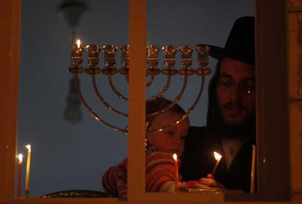 Israel, 20.12.2011 | Um judeu ultra-ortodoxo segura o filho enquanto acende uma vela para marcar o Hanukkah (o festival das luzes, de 20 a 28 de Dezembro), uma das mais importantes celebrações judaicas.