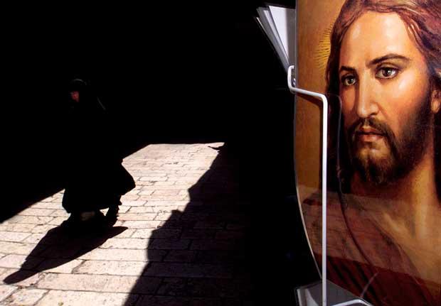 Uma freira cristã ortodoxa caminha por uma rua que leva ao Santo Sepulcro. Em primeiro plano, imagem de Jesus vista numa loja de souvenirs
