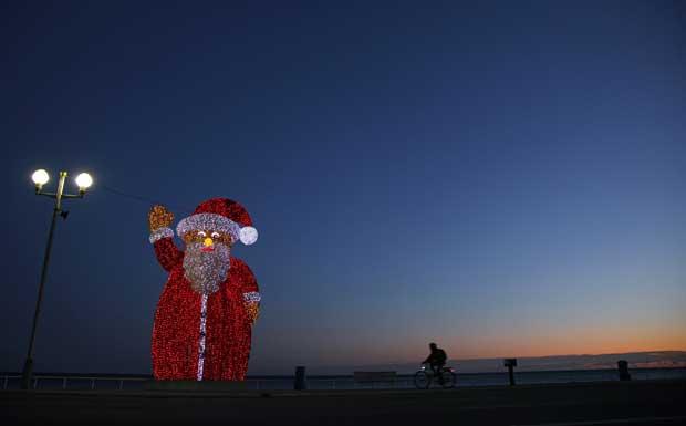França. Saudação de um Pai Natal luminoso na Promenade des Anglais de Nice