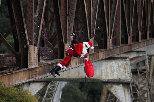 Guatemala. Um bombeiro vestido de Pai Natal desce preso por cabos ao bairro sobre a ponte para distribuir presentes às crianças pobres que aí vivem