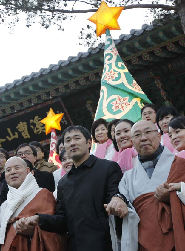 Coreia do Sul. O líder dos budistas sul-coreanos, um padre católico e crentes de ambas as fés dão as mãos durante um evento de inauguração das árvores de Natal colocadas no templo budista de Jogye. O objectivo é enaltecer a paz e concórdia entre as diferentes religiões.