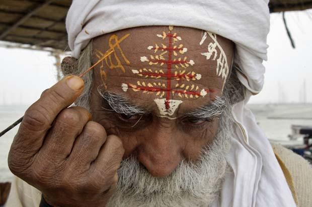 "Índia. Um hindu escreve ""Feliz Natal"" em hindi na testa, nas margens do rio Ganges, em Allahabad."