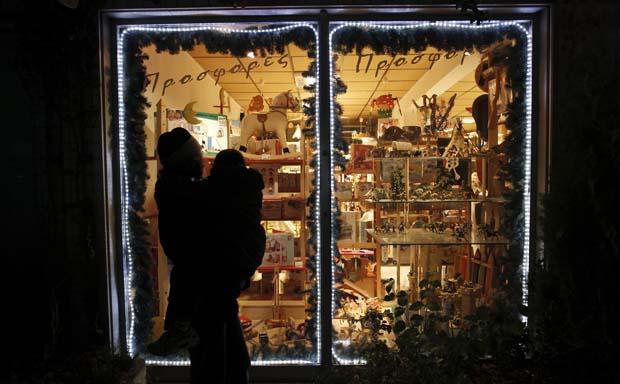 Grécia. Uma mãe com o filho ao colo espreitam a montra de uma loja de brinquedos em Atenas.