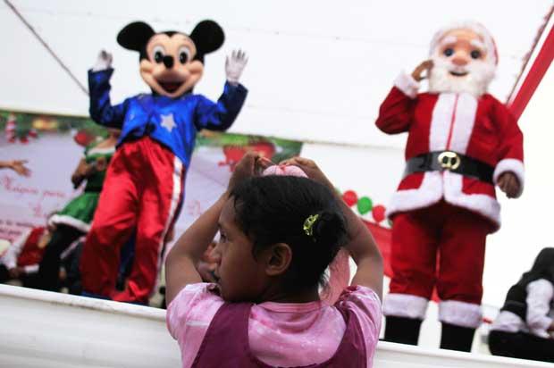 Peru. Mickey e o Pai Natal fazem as delícias desta pequena espectadora. Em Lima