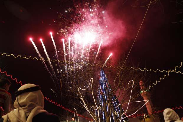 Cisjordânia, Belém. Palestinianos observam os fogos de artifício durante a cerimónia de iluminação da árvore de Natal no largo da Igreja da Natividade, o local venerado como o do nascimento de Jesus Cristo