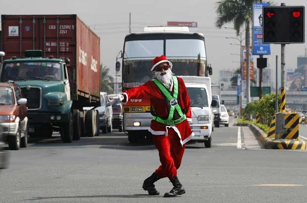 Filipinas. O controlador de tráfego Ramiro Hinojas, em Pasay, decidiu vestir-se de Pai Natal. Aqui, é visto reflectido no espelho lateral de um veículo