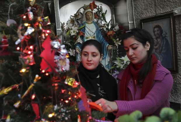 Jordânia. Jovens cristãs iraquianas, exiladas na Jordânia, decoram a árvore de Natal numa igreja em Amã