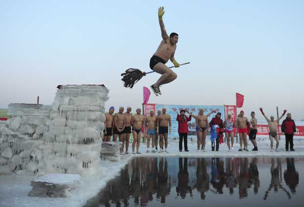 China, 26.12.2011 | Será só ilusão de óptica? Um membro de um clube de natação de Inverno salta para a água na sua vassoura. Em Harbin.